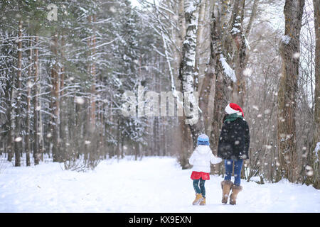 A winter fairy tale, a young mother and her daughter ride a sled - Stock Photo
