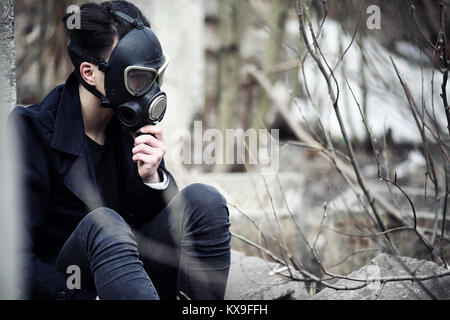 The guy in the coat and gas mask. Post-apocalyptic portrait of A - Stock Photo