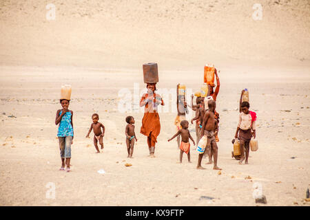 Himba woman and children working carrying water to a village of Himba tribe people indigenous to the Kunene Region, - Stock Photo