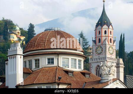 Italien, Südtirol, Meran, Kuppel des Kurhauses an der Passerpromenade und der Turm der spätgotischen Stadtpfarrkirche - Stock Photo