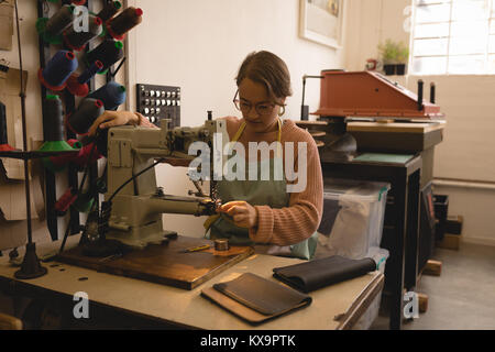 Worker putting thread into sewing machine - Stock Photo