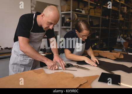 Workers measuring leather with ruler - Stock Photo