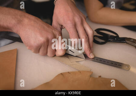 Worker cutting a leather with cutter - Stock Photo