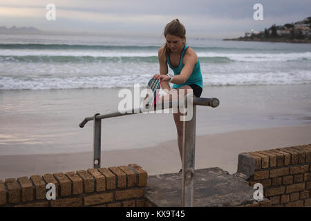 Woman performing stretching exercise near beach - Stock Photo