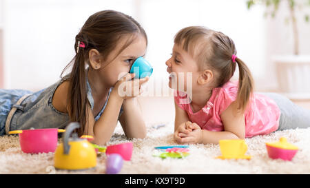 Cute funny children playing with toys on floor at home - Stock Photo