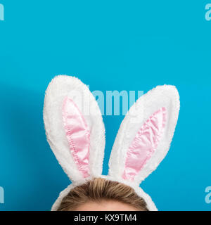Easter bunny ears. Female wearing white bunny ears costume against a bright blue background - Stock Photo