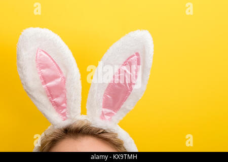 Easter bunny ears. Female wearing white bunny ears costume against a bright yellow background - Stock Photo