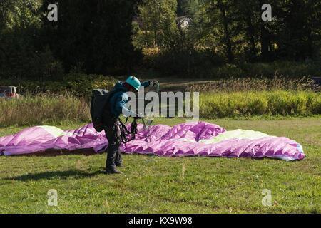 Paraglider landing on green landscape - Stock Photo