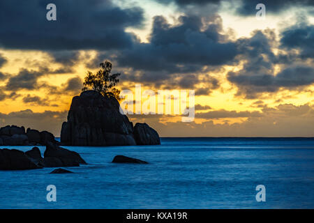 Mystic sunset over granite rocks in the water with a single tree at baie lazare on the seychelles - Stock Photo