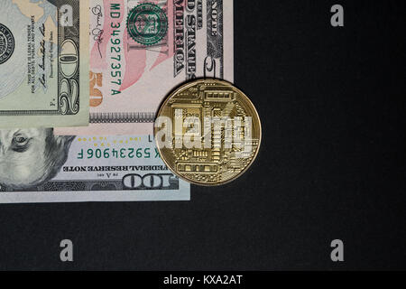 Golden bitcoin on dollar paper bills or banknotes with black text space area - Stock Photo