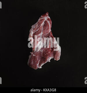 Food photo in rustic style. Raw meat. Pork steak on dark black background of slate plate. Top view. Flat lay. - Stock Photo