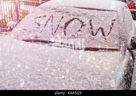 Snow covered car windscreen with the word snow written in the snow - Stock Photo