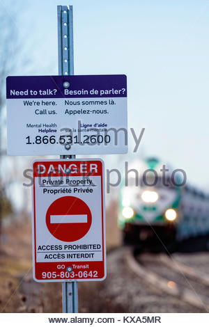 Suicide prevention sign at railway level crossing to prevent suicide by train in Ontario Canada - Stock Photo