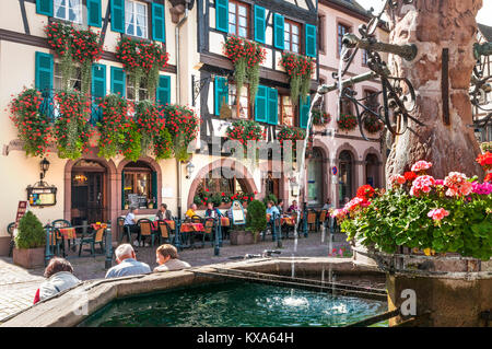 Kaysersberg Alfresco Bar Restaurant Alsace France Fountain in central square with restaurant Hotel Du Chateau behind - Stock Photo