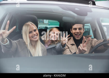 Picture of happy emotional young man sitting in car with his wife and daughter. Looking camera showing peace gesture. - Stock Photo