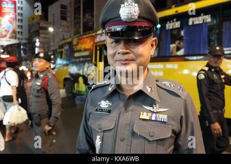 A Thai police officer patrols street food vendors in Chinatown, Bangkok, Thailand - Stock Photo