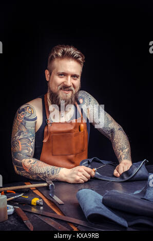 Currier of leather focusing on his work - Stock Photo