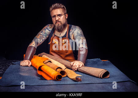 Leather Tanner working with leather using crafting tools at his desk - Stock Photo