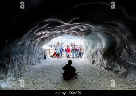 Tourists posing for photo in front of ice cave styled entrance, Chamonix Mont-Blanc, Haute Savoie, France - Stock Photo