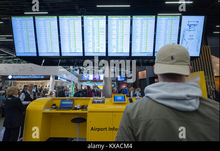 AMSTERDAM, NETHERLANDS - DEC 27, 2017: A man is looking at the information screens to check his flight on Schiphol - Stock Photo