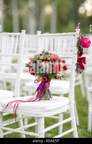Stunning red bridal bouquet on white chair. Wedding ceremony. Mix of succulents, orchids and roses - Stock Photo