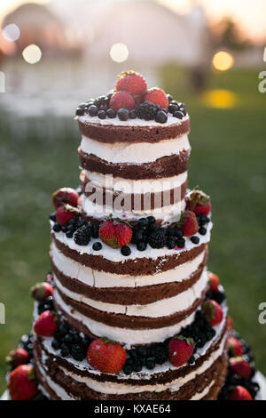 Round multi tiered wedding cake with sponge, cream, jam and berries on a circular base. Fresh blueberries and strawberries