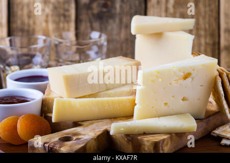 Cheese, fruit jam, nuts and wine on wooden cutting board, delicious holiday appetizer - Stock Photo