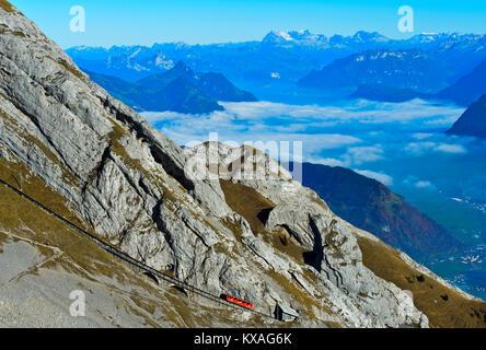 Red wagon of the Pilatus Railway at Mount Pilatus,mountain panorama in the background,Alpnachstad,Switzerland - Stock Photo