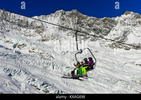 Skiers on a chairlift in front of the Feegletscher and the peaks Dom and Lenzspitze,Mischabel Group,Saas-Fee ski - Stock Photo