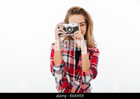Portrait of a young pretty girl in plaid shirt taking a photo with a retro camera isolated over white background - Stock Photo