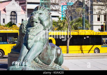 Wellington, New Zealand - 28 September, 2015: Bronze Lions at the base of the Wellington Cenotaph with city buses - Stock Photo