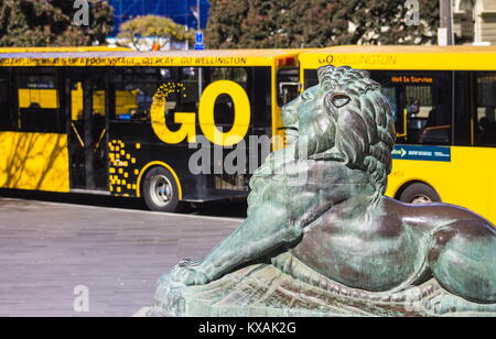Wellington, New Zealand - 28 September, 2015: Bronze Lion at the base of the Wellington Cenotaph with city buses - Stock Photo