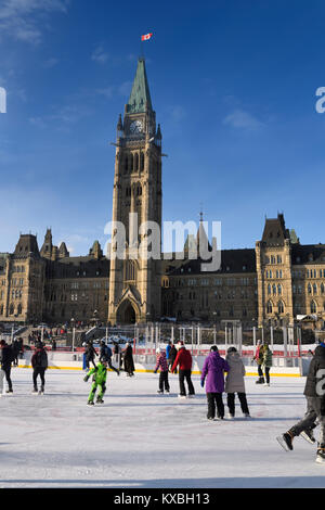 Parliament Hill Centre Block Peace Tower with afternoon sun on skaters on the free Canada 150 Rink refrigerated - Stock Photo