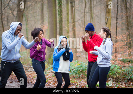 Determined young people warming up with boxing moves - Stock Photo