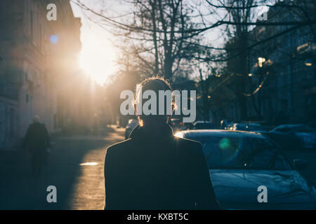 Woman in a black coat walks down the street in winter, view from the back - Stock Photo