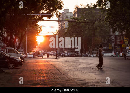 Some people and traffic on the Merchant Road at the downtown in Yangon (Rangoon), Myanmar (Burma), at sunrise. - Stock Photo