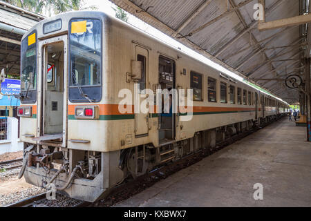 Commuter train and few people at the Central railway station in Yangon, Myanmar (Burma). - Stock Photo