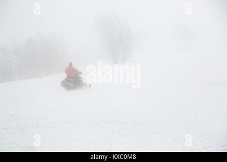 Snowmobile rider goes uphill in foggy weather. - Stock Photo