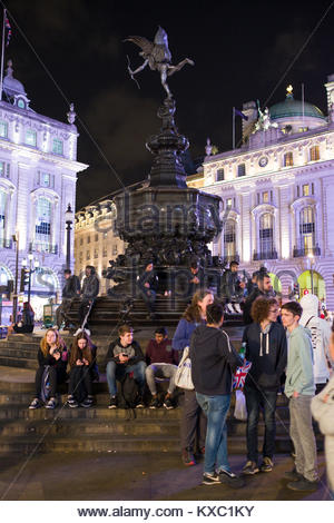 People around the Shaftesbury Memorial Fountain at night, the centerpiece of Piccadilly Circus public space, City - Stock Photo