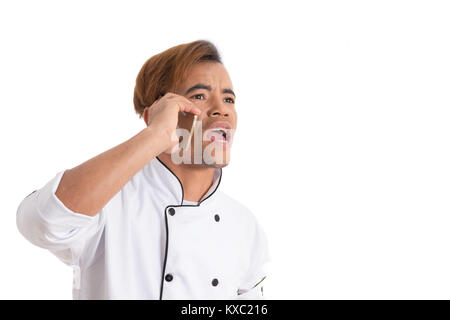Angry man is screaming and holds a cell phone. Young chef is in uniform. White background. - Stock Photo