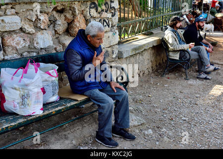 Older Greek man relaxing, sitting outside on bench with shopping bags, Athens, Greece - Stock Photo
