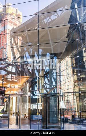 New York City, USA - October 27, 2017: NYC modern glass building entrance with woman walking inside in Chelsea West - Stock Photo