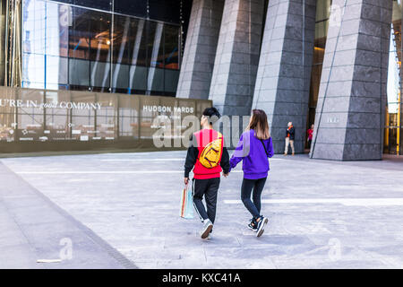 New York City, USA - October 27, 2017: NYC modern glass building entrance with young asian couple walking in Chelsea - Stock Photo