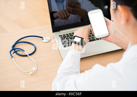 selective focus photo of online service doctor working in office and using mobile cell phone connecting smartwatch - Stock Photo