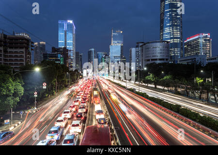 Light trails from heavy traffic along the Gatot Subroto highway in the heart of Jakarta business district at night. - Stock Photo