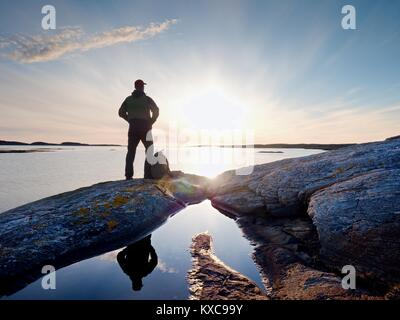 Young standing man with backpack. Hiker on the stone on the seashore at colorful sunset sky. Beautiful landscape - Stock Photo