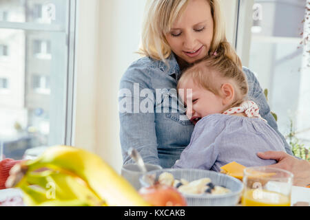 Little girl crying in mother's arms at breakfast table - Stock Photo
