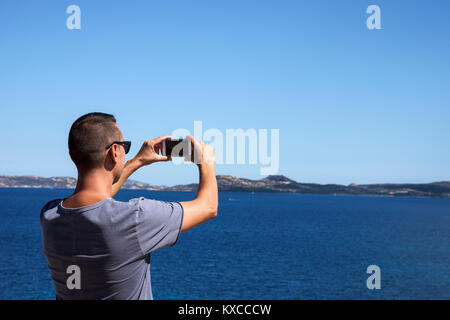 closeup of a young caucasian man seen from behind taking a photo of the sea in the Costa Smeralda, in Sardinia, - Stock Photo