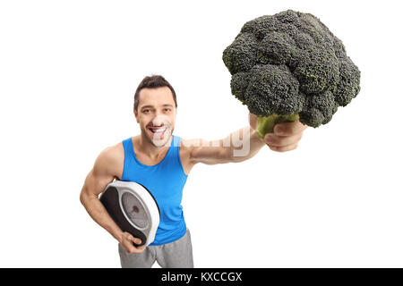 Athletic guy holding a weight scale and broccoli isolated on white background - Stock Photo