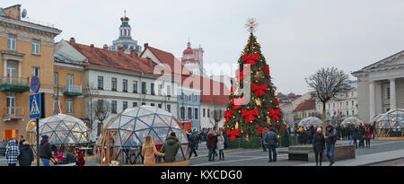 VILNIUS, LITHUANIA - DECEMBER 30, 2017:  Christmas tree in the Town Hall Square is decorated with red bows and light - Stock Photo